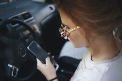 Envio de mensagem de texto louro atrativo da mulher em seu telefone celular ao conduzir imagem de stock
