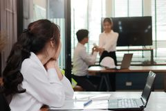 Envious angry Asian business woman looking affectionate couple in love in office. Jealousy and envy in friend relationship. Envious angry Asian business women Royalty Free Stock Images