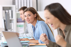 Envious employee looking at a successful colleague. Portrait of a envious employee looking at a successful colleague at office royalty free stock photos