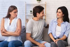 Envious Girl Looking At Flirting Couple Sitting On Sofa Indoor
