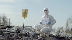 Enviroment pollution, Hazmat man into uniform shows sign save the planet on landfill with pointer biological hazard stock video
