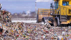 Enviromet pollution concept. Landfill tractor drives away near piles of trash. An orange landfill compactor moves away near unloaded waste piles stock footage