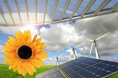 Environment. Sunflowers, solar pannels and wind turbines in a green field Royalty Free Stock Image