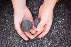 Environment. Child holding volcanic pebbles on seashore Royalty Free Stock Image