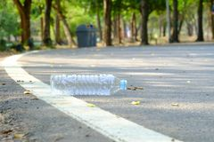 A bottle of drinking water littering on a road ground floor at the green park with blurred a trash bin in the sideway royalty free stock photos