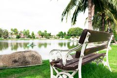 Environment of garden in the village with white metal benche and. White metal bench with old brown wooden broken seat beside the lake view Stock Image
