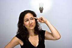 The environment idea!. Woman who just came up with a great environmentally friendly idea. Pointing up her finger at her head and having a compact fluorescent stock photography
