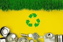 Green recycle sign with metal aluminium cans, covers, jars royalty free stock images