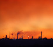 Environment pollution. Red sky over petrochemical factory chimneys Stock Photography
