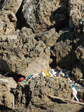Environment pollution. Pollution of the environment - Heap of garbage and plastic bottles thrown out in nature littering a rocky area Royalty Free Stock Photos