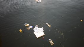 Environment pollution: Swirling Trash Floating in a river stock footage