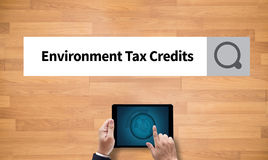 Environment Tax Credits Document Form Credits. On the tablet pc screen held by businessman hands - online, top view stock image