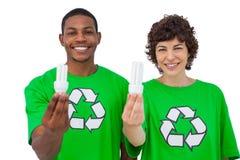 Environmental activists holding energy saving light bulbs Stock Photos