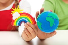 Environmental awareness and education concept. Child hands holding earth globe and rainbow made of clay Royalty Free Stock Photo