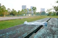 A plastic bottle of drinking water littering on old wooden seat at the outdoor stadium at the park with blurred a big building royalty free stock photos