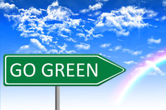 Environmental concept illustration, green traffic sign with go green message, blue clouds background with rainbow. Eco concept illustration, green traffic sign Royalty Free Stock Image