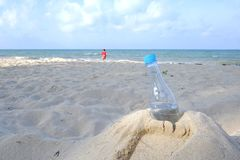 A plastic bottle of drinking water littering on the sand beach with a beautiful blue sea background stock photography