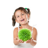 Environmental conservation. Little girl holding and offering a sphere of green grass, symbol of environmental conservation and responsibility, isolated on white Stock Image