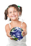 Environmental conservation. Happy smiling little girl holding and offering planet heart, symbol of environmental conservation and green attitude Royalty Free Stock Photography