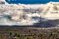 Environmental disaster. Copper plant in valley against the background of the mountains, toxic smoke from the pipes, dramatic rain. Environmental disaster. Copper stock photo