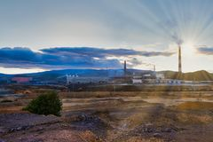 Environmental disaster. Copper plant in the valley against the background of the mountains, toxic smoke from the pipes,. Environmental disaster. Copper plant in stock images