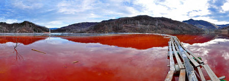 Environmental disaster. Panorama of a lake full with contaminate. D water from a mine in Geamana, Rosia Montana, Romania royalty free stock image