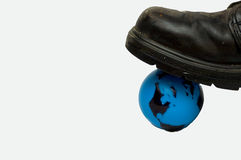 Environmental Footprint Black Boot. Concept picture with a black boot stepping on a blue plastic Earth globe Stock Images