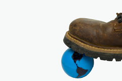 Environmental Footprint Brown Boot. Concept picture with a brown boot stepping on a blue plastic Earth globe Royalty Free Stock Photography