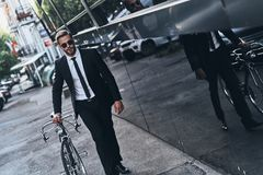 Environmental friendly. Handsome young man in full suit pulling his bicycle while walking outdoors royalty free stock photography