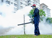 Environmental health workers. PUTRAJAYA, MALAYSIA - Feb. 4:Unidentified man is implementing fogging for dengue preventive at evening on February 4, 2012 in Royalty Free Stock Image