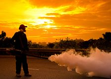 Environmental health workers. PUTRAJAYA, MALAYSIA - Feb. 4:Unidentified man is implementing fogging for dengue preventive at evening on February 4, 2012 in Stock Photo