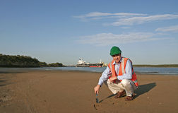 Environmental healths check. An environmental engineer, wearing protective clothing, taking a soil sample, with a beautiful blue sky behind him and a large ship royalty free stock photo