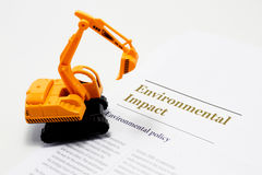 Environmental Impact. Picture illustrating the environmental impact and environmental policy. Image contains a construction vehicle backhoe Stock Image