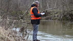 Environmental inspector checks the river pollution in early spring stock video