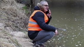 Environmental inspector talking on smartphone near the river in early spring stock footage