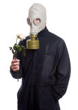 Environmental Issues. A guy wearing a gas mask is holding a wilting rose, isolated against a white background Stock Image