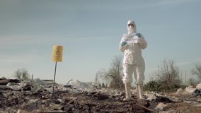 Environmental movement, girl in mask and costume holding poster with stop pollution slogan at trash dump with sign stock video