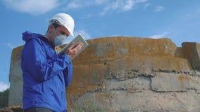 Environmental pollution. man chemist scientist in a respirator mask studies landfill dump pollution radioactive waste