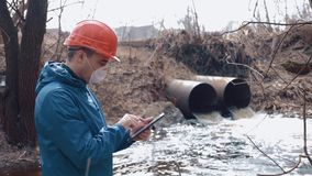 Environmental pollution. A man in a helmet and respirator with a tablet measures the level of pollution of waste water stock footage