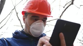 Environmental pollution. A man in a helmet and respirator with a tablet measures the level of pollution of waste water stock video footage