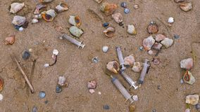 Medical syringes among the rapan shells in sand on sea beach after storm. Environmental pollution by medical and household waste stock video footage