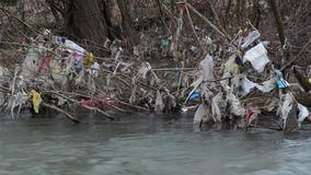 Environmental pollution. Plastic bags, bottles, trash and garbage floating in polluted river. Rubbish and waste in water. Heavy co. Ntaminated river bank stock video footage