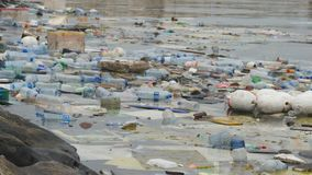Environmental pollution. Plastic bottles, bags, trash in river, lake. Rubbish and pollution floating in water.  stock video