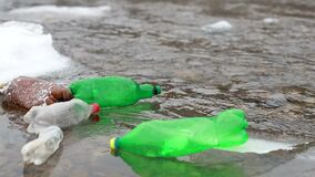 Environmental pollution. Plastic bottles, bags, trash in river, lake. Rubbish and pollution floating in water. Slow