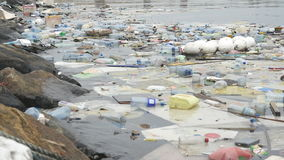 Environmental pollution. Plastic bottles, bags, trash in river, lake. Rubbish and pollution floating in water. Slow stock video