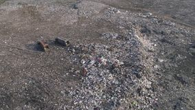 Environmental pollution problem, drone view on people work at dump near trucks and flying seagulls over large rubbish