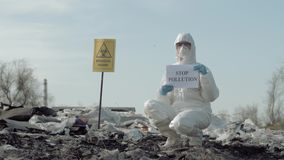 Environmental pollution problem, Hazmat Worker into protective clothing shows sign stop pollution on rubbish dump with stock video