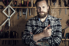 Environmental portrait of a man smoking pipe in wood workshop Royalty Free Stock Images
