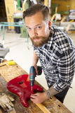 Environmental portrait of man working in workshop with guitar Stock Photography