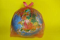 Environmental Problems, Nature Pollution And Ecology Concept. Abstract Background. Globe In The Plastic Bag Over Yellow Background. Environmental Problems stock photo